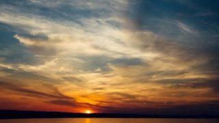 Die Sonne geht über einem See unter