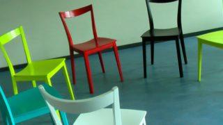 Vier bunte Stühle stehen im Halbkreis