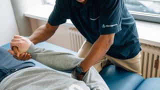 Therapeut mit Patient in der Physiotherapie der Pfennigparade