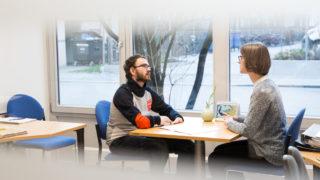 Zwei Personen sitzen sich gegenüber und führen ein Gespräch