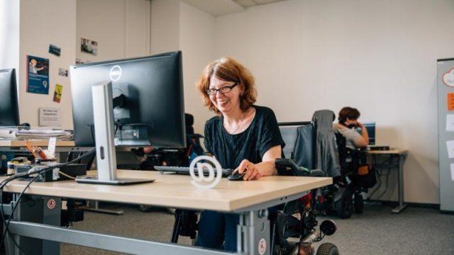 Eine Frau im Rollstuhl an Ihrem Computerarbeitsplatz