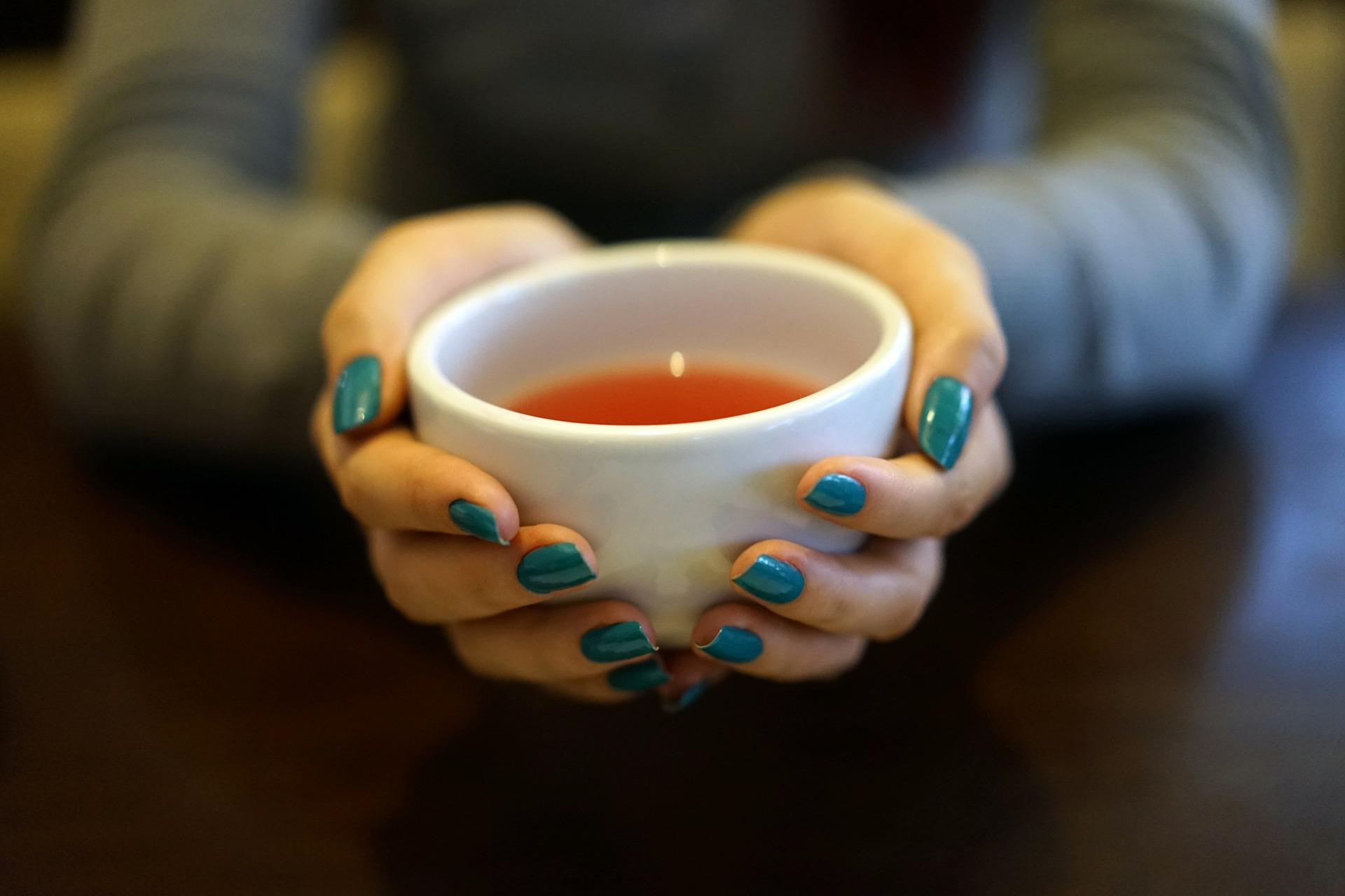 Hände halten Teetasse